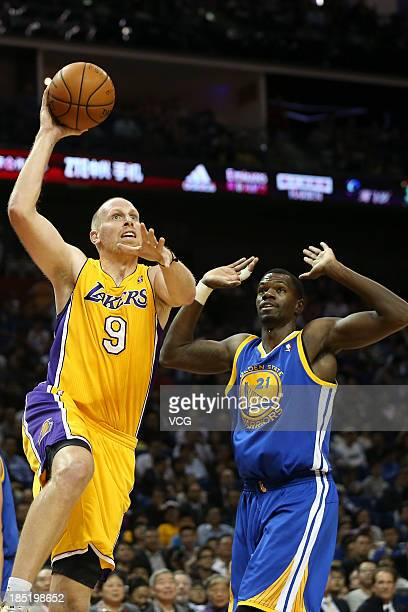 Chris Kaman of the Los Angeles Lakers goes to the basket against Dewayne Dedmon of the Golden State Warriors during the 2013 Global Games at the...