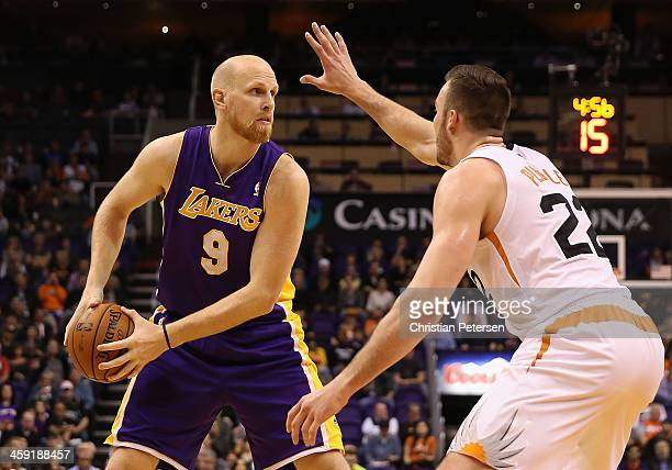 Chris Kaman of the Los Angeles Lakers looks to pass guarded by Miles Plumlee of the Phoenix Suns during the first half of the NBA game at US Airways...