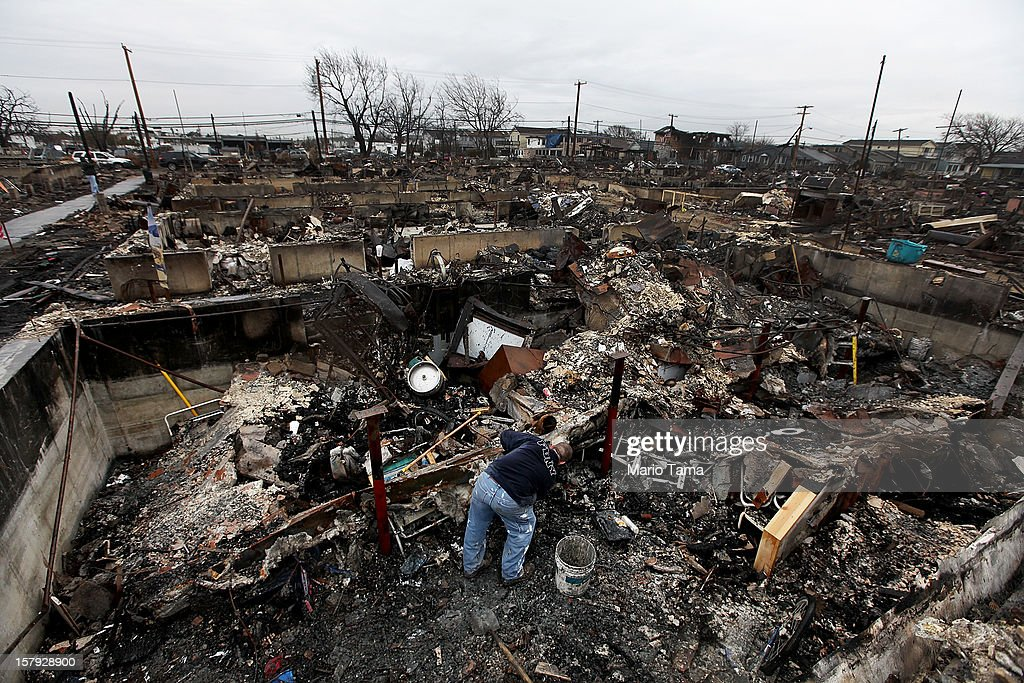 Chris Kane clears debris from the charred remains of his father's destroyed home in the hard hit Breezy Point neighborhood on December 7, 2012 in the Queens borough of New York City. Breezy Point, home to many New York City firefighters and police, lost 111 homes in a fast moving fire during Superstorm Sandy with many more homes severely damaged from flooding.