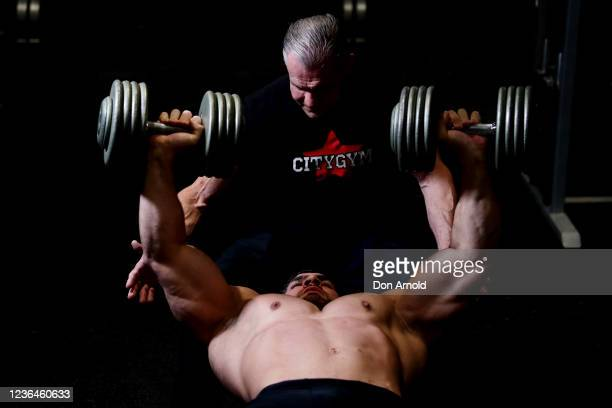Chris Kavvalos performs a dumbbell chest press with assistance from PT Paul Haslam during a workout at City Gym on May 24, 2020 in Sydney, Australia....