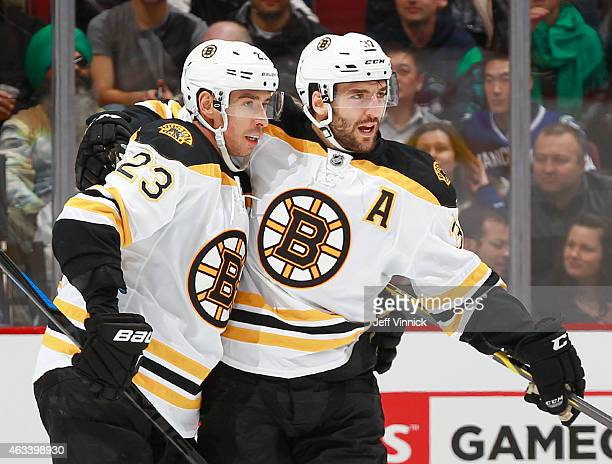 Chris Kelly congratulates Patrice Bergeron of the Boston Bruins who scored against the Vancouver Canucks during their NHL game at Rogers Arena...