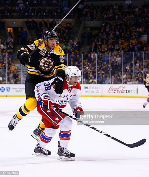 Chris Kelly of the Boston Bruins attempts to jump around Jack Hillen of the Washington Capitals in the first period during the game at TD Garden on...