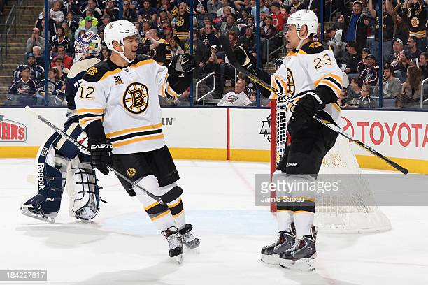 Chris Kelly of the Boston Bruins celebrates with teammate Jarome Iginla of the Boston Bruins after scoring a goal during the second period on October...