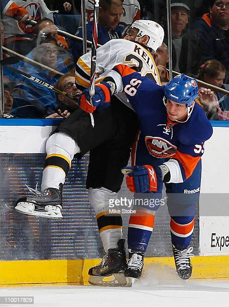Chris Kelly of the Boston Bruins gets checked hard into the boards by Michael Haley of the New York Islanders on March 11, 2011 at Nassau Coliseum in...
