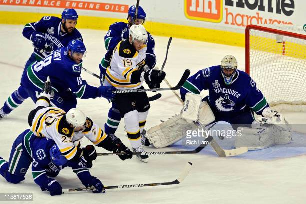 Chris Kelly of the Boston Bruins goes over the top of Manny Malhotra of the Vancouver Canucks as Roberto Luongo prepares to make a save during Game...