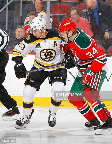 Chris Kelly of the Boston Bruins in action against Jon Merrill of the New Jersey Devils at the Prudential Center on March 18 2014 in Newark New...