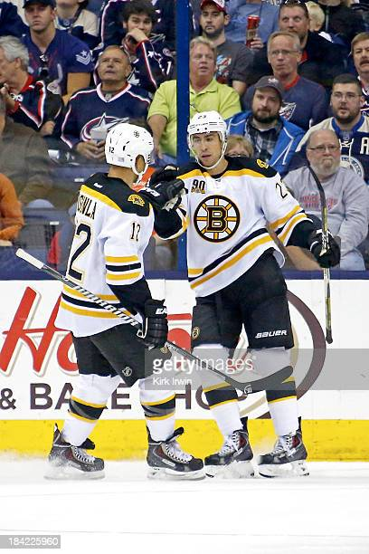 Chris Kelly of the Boston Bruins is congratulated by Jarome Iginla of the Boston Bruins after scoring a goal during the second period against the...