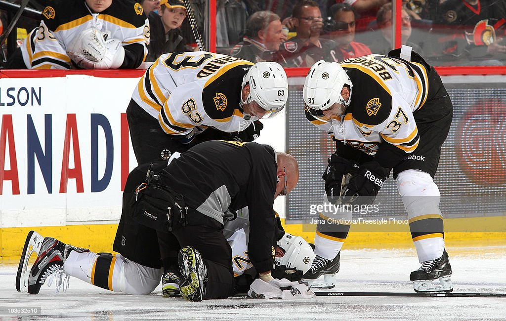Chris Kelly #23 of the Boston Bruins lies on the ice as team therapist and team mates Brad Marchand #63 and Patrice Bergeron #37 look on, during an NHL game at Scotiabank Place, on March 11, 2013 in Ottawa, Ontario, Canada.