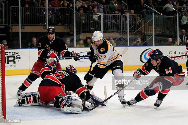 Chris Kelly of the Boston Bruins shoots against Henrik Lundqvist of the New York Rangers and Ryan Callahan of the New York Rangers at Madison Square...