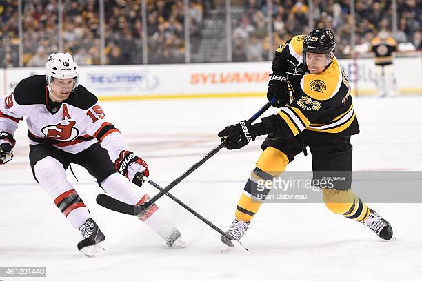 Chris Kelly of the Boston Bruins shoots the puck against Travis Zajac of the New Jersey Devils at the TD Garden on January 8 2015 in Boston...