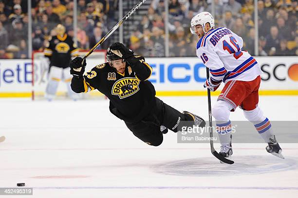 Chris Kelly of the Boston Bruins skates after the puck against Derick Brassard of the New York Rangers at the TD Garden on November 29 2013 in Boston...