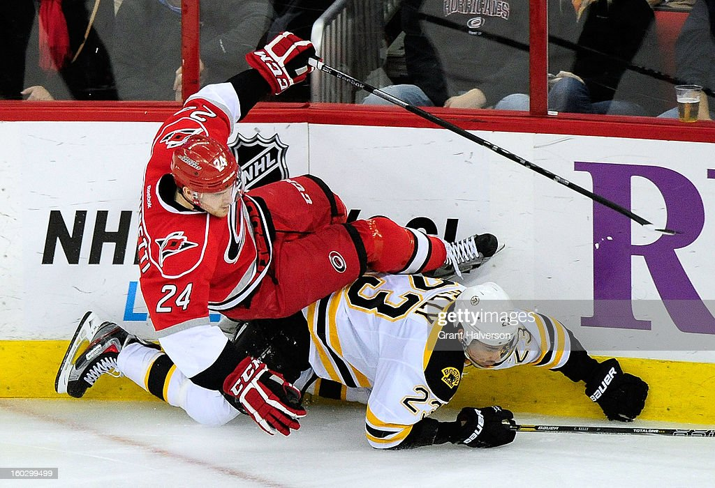 Chris Kelly #23 of the Boston Bruins upends Bobby Sanguinetti #24 of the Carolina Hurricanes during play at PNC Arena on January 28, 2013 in Raleigh, North Carolina. The Bruins defeated the Hurricanes, 5-3.