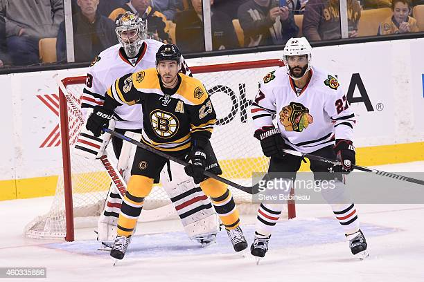 Chris Kelly of the Boston Bruins watches the play against Scott Darling and Johnny Oduya of the Chicago Blackhawks at the TD Garden on December 11...