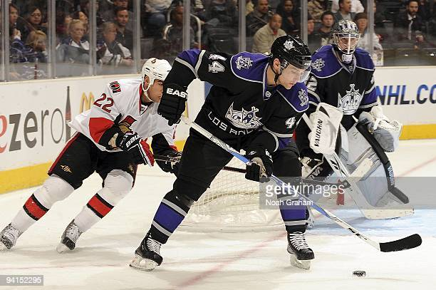 Chris Kelly of the Ottawa Senators defends from behind against Justin Williams of the Los Angeles Kings as he handles the puck during the game on...