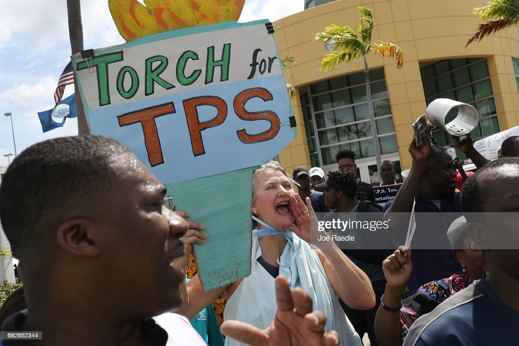 Chris Kirchner (C) joins others as they protest the possibility that the Trump administration may overturn the Temporary Protected Status for Haitians in front of the U.S. Citizenship and Immigration Services office on May 13, 2017 in Miami, Florida. 50,000 Haitians have been eligible for TPS and now the Trump administration has until May 23 to make a decision on extending TPS for Haitians or allowing it to expire on July 22 which would mean possibly deportation for the current TPS holders.
