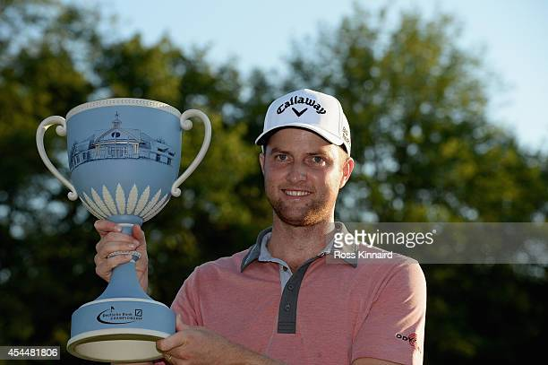 Chris Kirk is presented with the winner's trophy after winning the Deutsche Bank Championship at the TPC Boston on September 1 2014 in Norton...