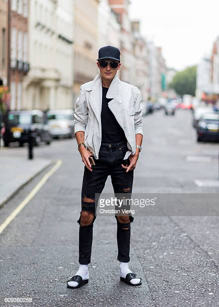 Chris Kowalski wearing a ripped denim jeans bathing shoes a black cap and white jacket outside Marques Almeida during London Fashion Week...