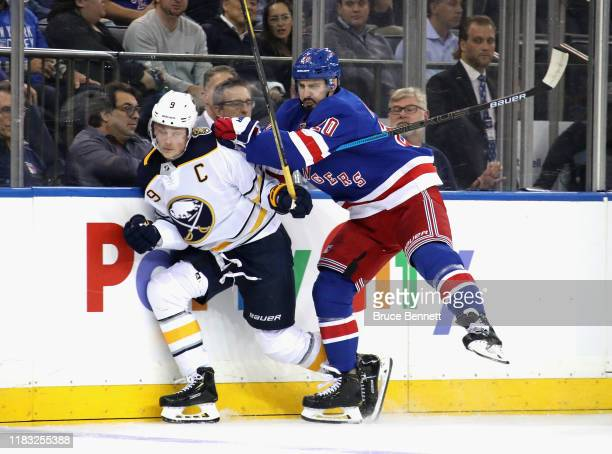 Chris Kreider of the New York Rangers checks Jack Eichel of the Buffalo Sabres into the boards during the second period at Madison Square Garden on...