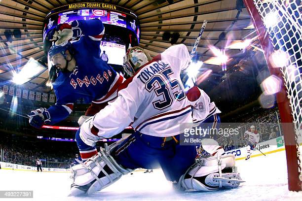 Chris Kreider of the New York Rangers crashes into Dustin Tokarski of the Montreal Canadiens in Game Three of the Eastern Conference Final during the...