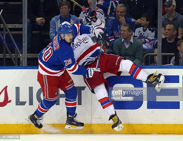 Chris Kreider of the New York Rangers hots Alex Ovechkin of the Washington Capitals into the boards during the first period in Game Two of the...