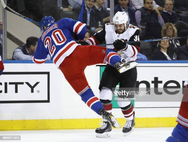Chris Kreider of the New York Rangers is hit by Zac Rinaldo of the Arizona Coyotes during the first period at Madison Square Garden on October 26...