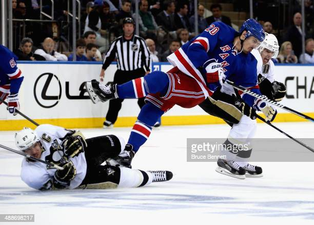 Chris Kreider of the New York Rangers is sent flying into the air over Sidney Crosby of the Pittsburgh Penguins as teamate Evgeni Malkin skates...
