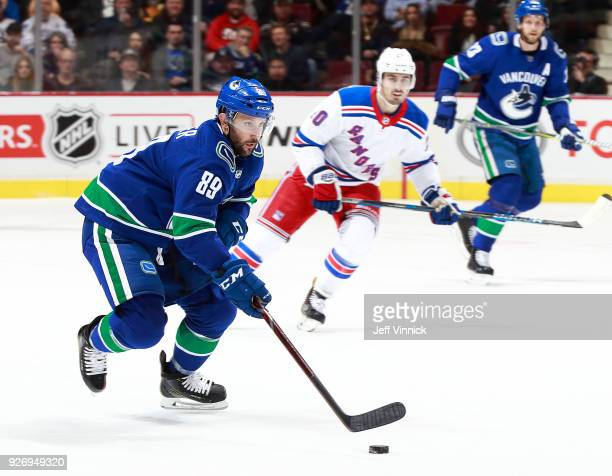Chris Kreider of the New York Rangers looks on as Sam Gagner of the Vancouver Canucks skates up ice with the puck during their NHL game at Rogers...