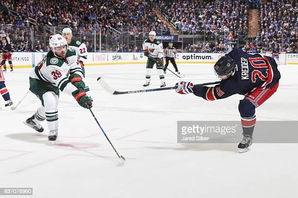Chris Kreider of the New York Rangers shoots the puck against Nate Prosser of the Minnesota Wild at Madison Square Garden on December 23 2016 in New...