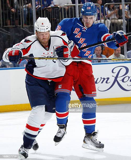 Chris Kreider of the New York Rangers throws a check on John Erskine of the Washington Capitals in Game Six of the Eastern Conference Quarterfinals...