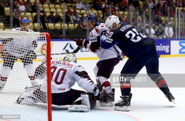 Chris Kreider of United States and Kristaps Sotnieks of Latvia battle for the puck during the 2018 IIHF Ice Hockey World Championship Group B game...