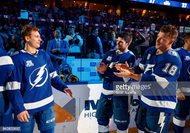 Chris Kunitz and Ondrej Palat of the Tampa Bay Lightning applaud teammate Yanni Gourde after being named one of the stars of the game after the win...