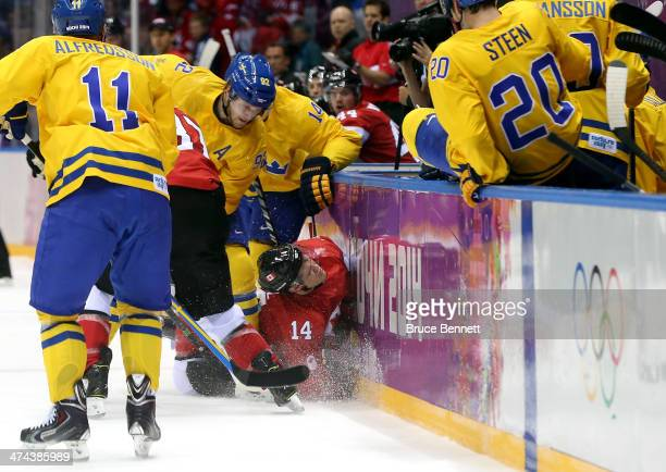 Chris Kunitz of Canada crashes into the boards against Gabriel Landeskog and Patrik Berglund of Sweden during the Men's Ice Hockey Gold Medal match...