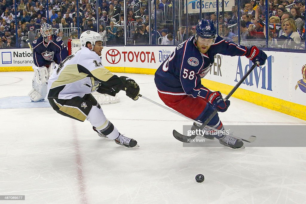 Chris Kunitz #14 of the Pittsburgh Penguins and David Savard #58 of the Columbus Blue Jackets battle for control of the puck during Game Four of the First Round of the 2014 NHL Stanley Cup Playoffs at Nationwide Arena on April 23, 2014 in Columbus, Ohio.
