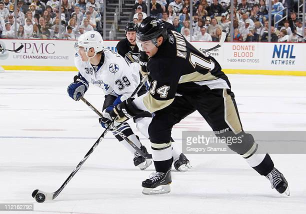 Chris Kunitz of the Pittsburgh Penguins controls the puck in front of Mike Lundin of the Tampa Bay Lightning in Game One of the Eastern Conference...