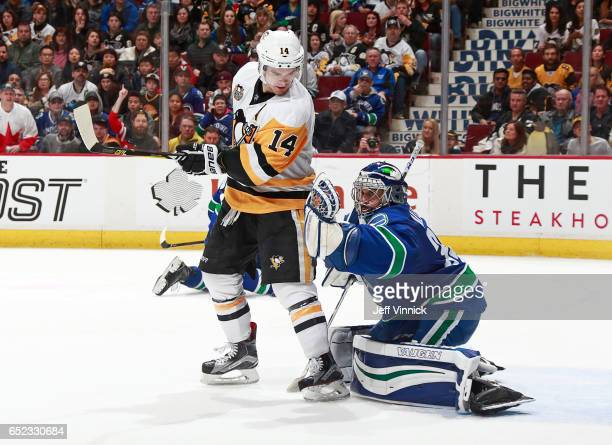 Chris Kunitz of the Pittsburgh Penguins looks on as Ryan Miller of the Vancouver Canucks makes a glove save during their NHL game at Rogers Arena...
