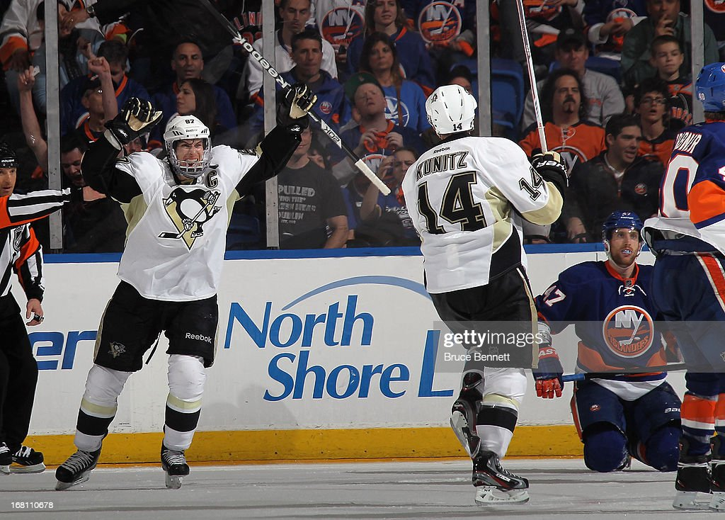 Chris Kunitz #14 of the Pittsburgh Penguins scores the overtime game winning powerplay goal at 8:44 against the New York Islanders and is joined by Sidney Crosby #87 (L) in Game Three of the Eastern Conference Quarterfinals during the 2013 NHL Stanley Cup Playoffs at the Nassau Veterans Memorial Coliseum on May 5, 2013 in Uniondale, New York. The Penguins defeated the Islanders 5-4 in overtime.