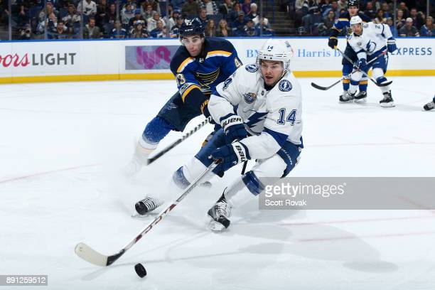 Chris Kunitz of the Tampa Bay Lightning handles the puck as Jordan Schmaltz of the St Louis Blues pressures at Scottrade Center on December 12 2017...