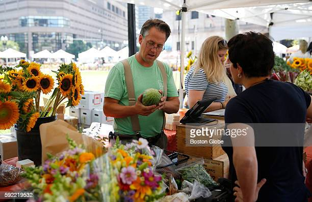 Chris Kurth owner of Siena Farms chats with a customer at the Copley Square Farmers Market in Boston Mass July 26 2016