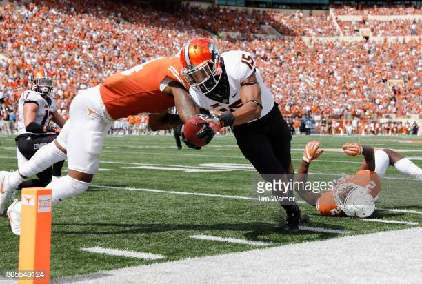Chris Lacy of the Oklahoma State Cowboys dives for the end zone defended by DeShon Elliott of the Texas Longhorns in the second half at Darrell K...