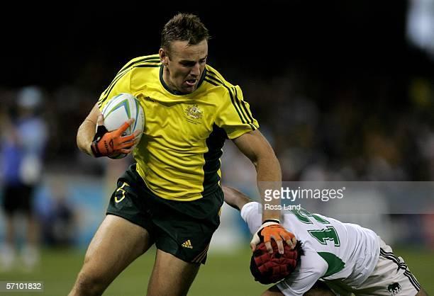 Chris Latham of Australia pushes the tackle away from Saliya Kumara of Sri Lanka during the rugby sevens match between Australia and Sri Lanka at the...