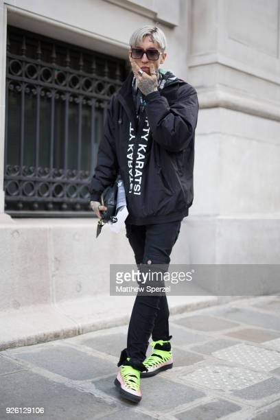 Chris Lavish is seen on the street attending Anrealage during Paris Fashion Week Women's A/W 2018 Collection wearing a black jacket with neon green...