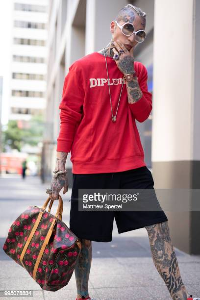Chris Lavish is seen on the street attending Men's New York Fashion Week wearing a Diplomacy shirt and shorts a Louis Vuitton bag Balenciaga...