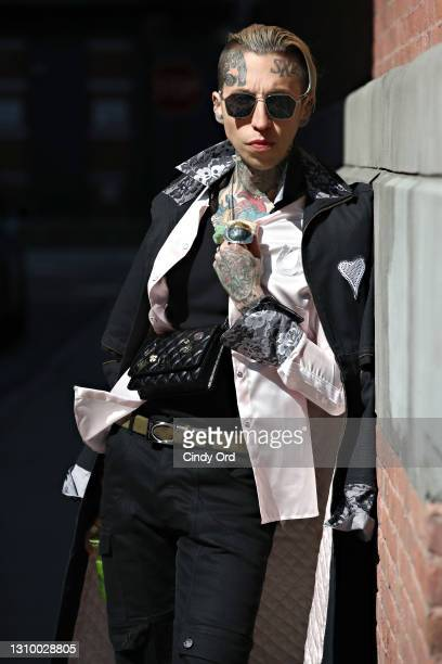 Chris Lavish wears Fendi sunglasses, a black Ears of Buddha Sustainably Stylish Upcycled Duster trench coat, a pink satin Ears of Buddha shirt, a...