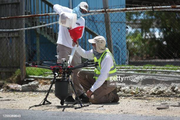 Chris Law and Bruce Stevens from the Florida Keys mosquito control department load a drone with BTI larvicide to be spread over an area as they work...