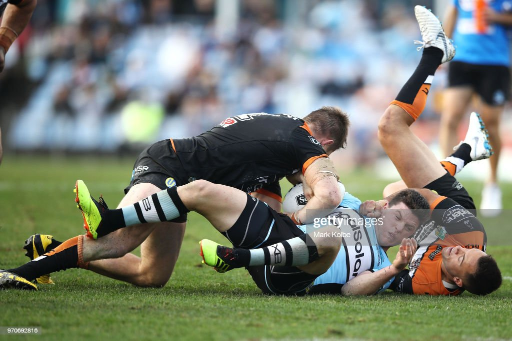 Chris Lawrence (L) and Luke Brooks (R) of the Tigers tackle Chad Townsend of the Sharks during the round 14 NRL match between the Cronulla Sharks and the Wests Tigers at Southern Cross Group Stadium on June 10, 2018 in Sydney, Australia.