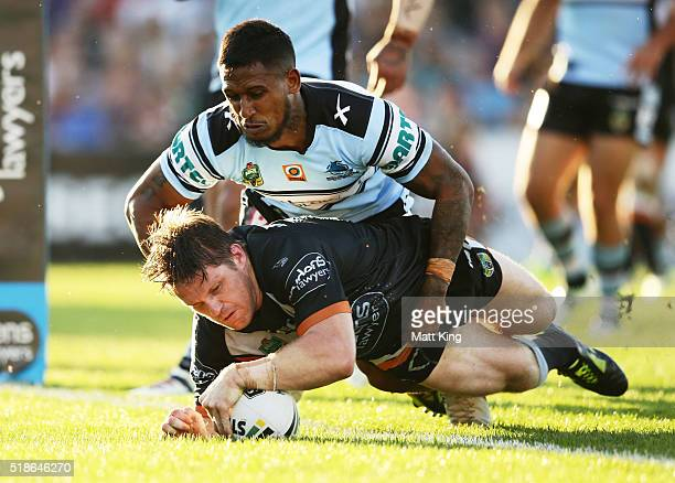 Chris Lawrence of the Tigers beats Ben Barba of the Sharks to score a try during the round five NRL match between the Wests Tigers and the Cronulla...
