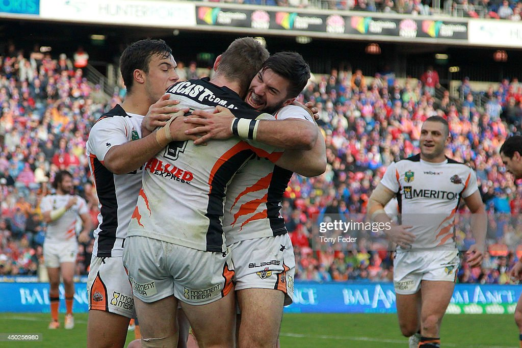 Chris Lawrence of the Tigers celebrates a try with team mate James Tedesco during the round 13 NRL match between the Newcastle Knights and the Wests Tigers at Hunter Stadium on June 8, 2014 in Newcastle, Australia.