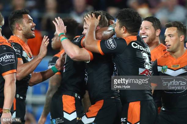 Chris Lawrence of the Tigers celebrates with team mates after scoring a try during the round 21 NRL match between the Gold Coast Titans and the Wests...
