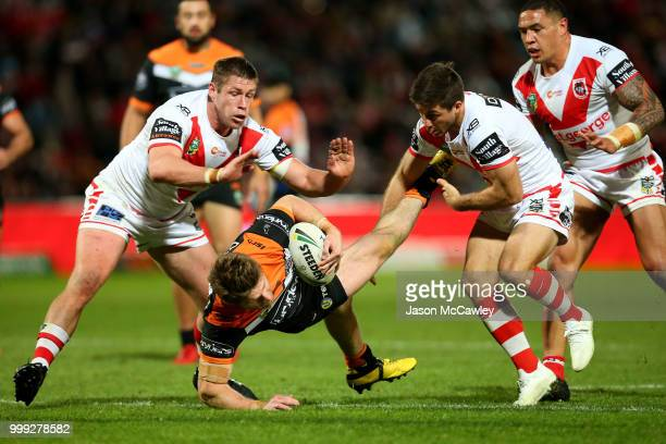 Chris Lawrence of the Tigers is tackled by Ben Hunt and Jeremy Latimore of the Dragons during the round 18 NRL match between the St George Illawarra...