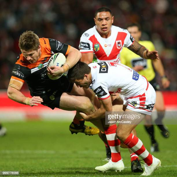 Chris Lawrence of the Tigers is tackled by Ben Hunt of the Dragons during the round 18 NRL match between the St George Illawarra Dragons and the...